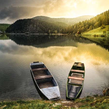Zwei alte Boote an einer Küste von einem See reflektieren warmes Licht der aufgehenden Sonne (Dedinky Dorf am Palcmanska Masa Wasserreservoir, Slowakei)