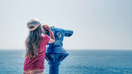 Young long blond hair girl wearing red shirt and white cap observing a sea via a blue telescope