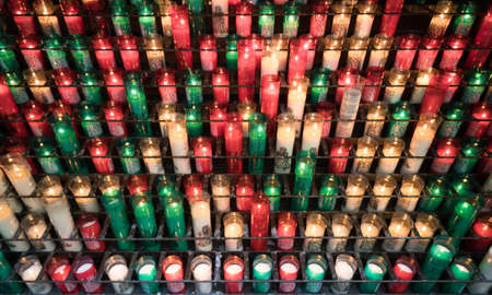 Rows of burning sacrificial candles in different colors