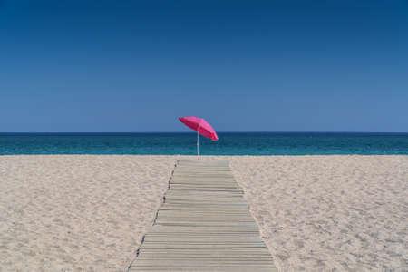 백그라운드에서 맑은 바닷물과 빈 모래 사장에 목조 포장의 끝에 혼자 서 태양 우산
