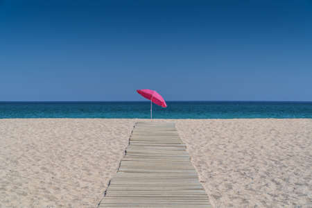 Sun umbrella standing alone at the end of a wooden pavement on an empty sandy beach with crystal clear sea waters in background