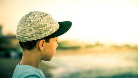 Over ths shoulder shot of a young boy wearing a sport cap and looking into the distance