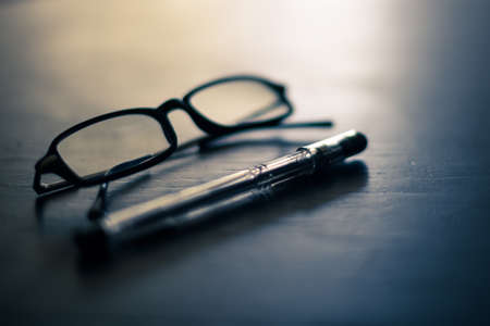 Glasses and pen on a table Standard-Bild