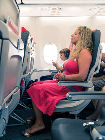 Flying with children: mother sitting in a plane with young boy wearing headphones and using his smartphone Standard-Bild