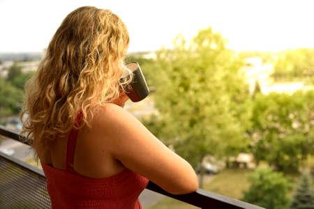 Pohled zezadu ženy, která pije horkou kávu s výhledem na východ slunce z balkonu