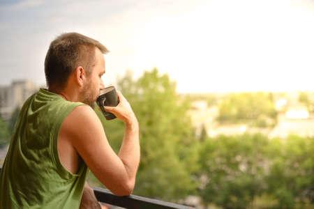 Mann mit Kaffee auf einem Balkon