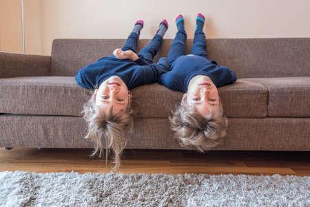 머리에 매달려있는 소파에 누워 두 어린 아이