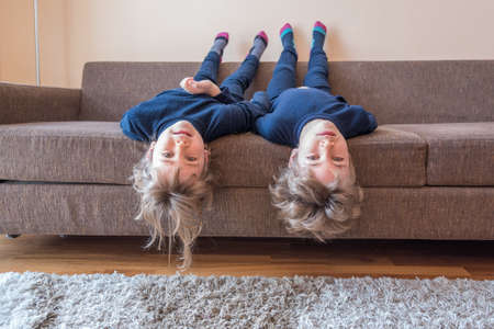 Two little children lying on a couch with heads hanging down