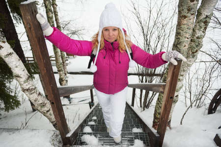 Yount woman in winter suit standing on stairs