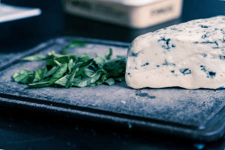 Blue cheese with spinach on cutting board Reklamní fotografie