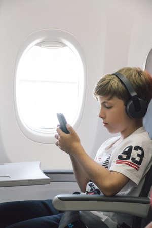 비행기에서 음악을 듣는 소년