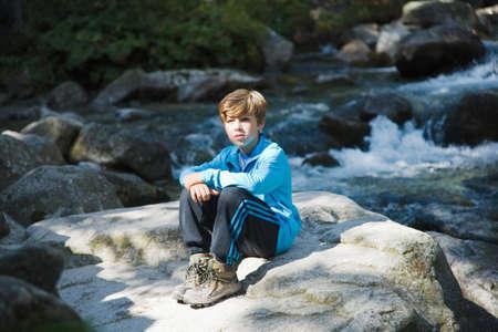 강가에 앉아있는 소년 스톡 콘텐츠
