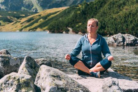 Žena meditace u jezera Reklamní fotografie