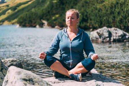 Woman meditating at the lake