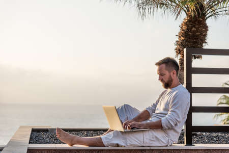 Young man with laptop at sunset Standard-Bild