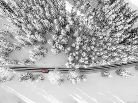 Road to nowhere. A car driving through a snowy road.