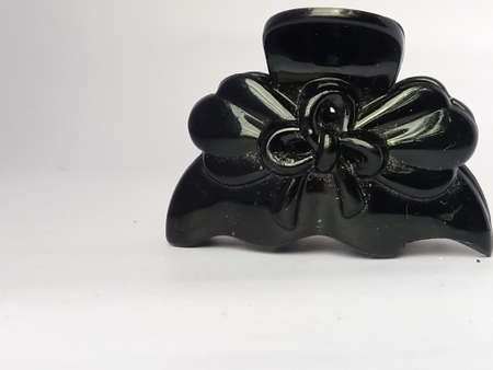 The front view of a decorated hair clip placed isolated in a white background.The clip has a flower design on its side.The black color shines under the light. Stockfoto