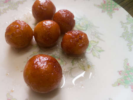 Gulab Jamun balls with sugar syrup placed in a white plate.They are made of bread while homemade.They are deep fried dumplings made of dried milk and dipped in rose cardamom flavored sugar syrup. Stock fotó - 152491959