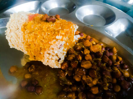 Kerala traditional food puttu and kadala in a steel plate.The bengal gram has black color and the puttu is made of wheat.We also see the coconut used in it. Stock fotó - 152492937