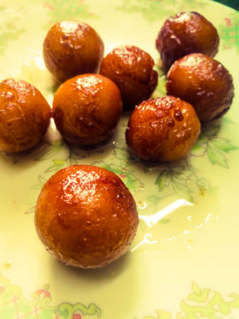 Gulab Jamun balls with sugar syrup placed in a white plate.They are made of bread while homemade.They are deep fried dumplings made of fried milk and dipped in rose cardamom flavored sugar syrup.