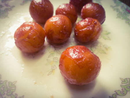 Gulab Jamun balls with sugar syrup placed in a white plate.They are made of bread while homemade.They are deep fried dumplings made of dried milk and dipped in rose cardamom flavored sugar syrup. Banco de Imagens