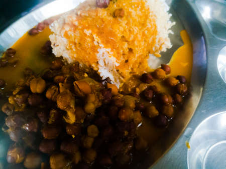 Kerala Traditional food puttu and Kadala curry in a steel plate.The bengal gram has black color and puttu is made of wheat.We also see the coconut used with it. Stock fotó - 152492362