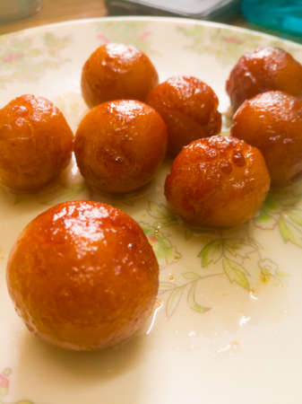 Gulab Jamun balls with sugar syrup placed in a white plate.They are made of bread while homemade.they are deep fried dumplings made of fried milk and dipped in rose cardamom flavored sugar syrup. Banco de Imagens