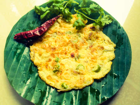 Omelette with coriander leaves and Red chillies in a banana leaf.The banana leaf has green color and the chillies are red in color and the omelette is fried well.The banana leaf has lines on it Imagens