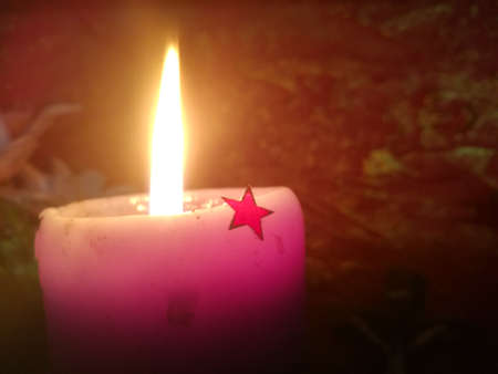 Lightening candle with fire and a decorating star on its body.The candle has pink color in its light.The star has a red color.The light spreads to the surroundings.