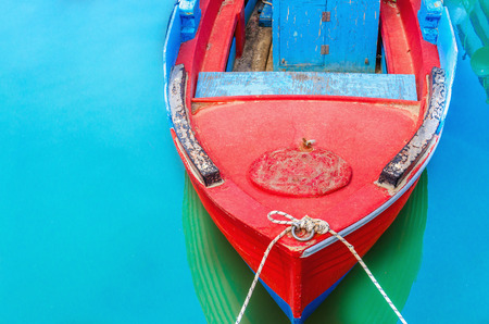 broadside: Empty red wooden boat with blue broadside moored in port with silent azure water Stock Photo