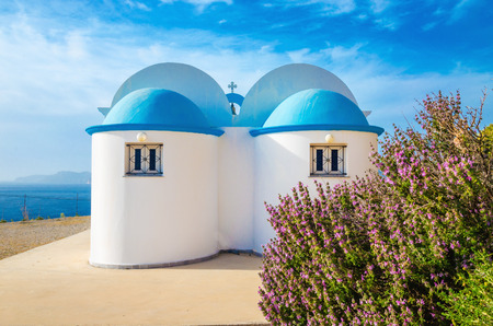 A view of a church with iconic blue roof and see in the background on Greek island, Kalymnos, Greece Standard-Bild
