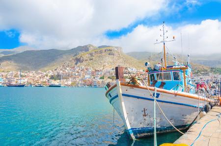 De boot die van typische Griekse Fishermans zich in haven met de havenbouw bevinden in backgound op Grieks Eiland, Griekenland