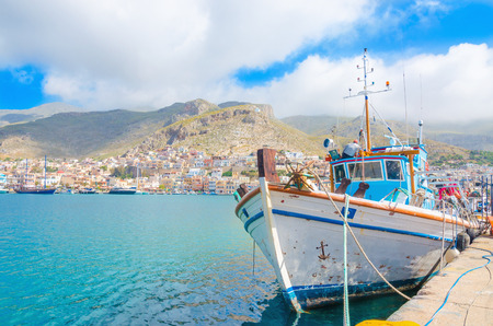 Typical Greek Fishermans boat standing in harbour with port building in backgound on Greek Island, Greece