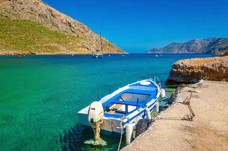 ionian island: Small open-deck motor boat in Greek colors in port at the bay of Greek Island, Greece Stock Photo