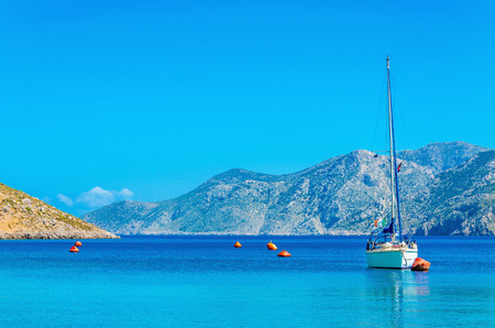 Sport yacht on anchor in silent bay on Greek Island, Greece