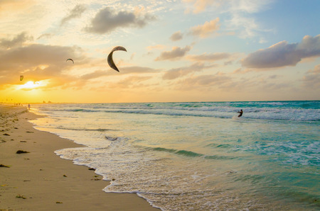 Professional kiter makes the difficult trick on a beautiful background of spray and beautiful sunset