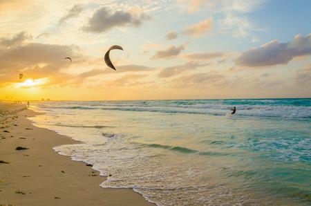 Professional kiter maakt de moeilijke truc op een mooie achtergrond van de spray en prachtige zonsondergang Stockfoto