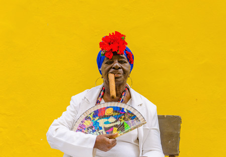 HAVANA, CUBA - DECEMBER 2, 2013: Old black lady dressed in typical cuban clothes smoking a huge cuban cigar against yellow wall in Havana.