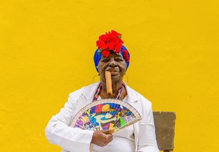 LA HABANA, CUBA - 2 de diciembre, 2013: La señora mayor negro vestido con ropas típicas cubanas fumando un enorme puro cubano contra la pared amarilla en La Habana.