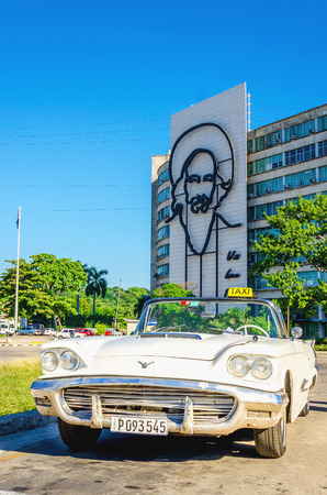 HAVANA, CUBA - DECEMBER 2, 2013: American classic white cabriolet o the background of Ministry of the Interior building with face of Fidel Castro located in Revolution Square, Havana, Cuba