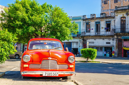 HAVANA, CUBA - DECEMBER 2, 2013: Classic American red car one of streets in Havana, where old cars bought before Cuban revolution are icon view of Cuba