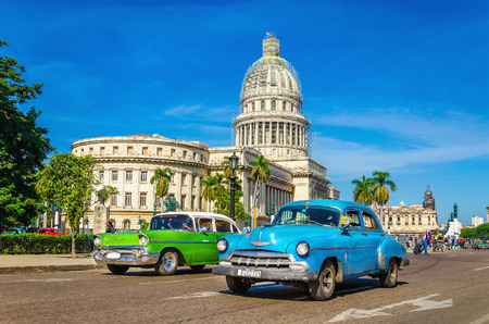 HAVANA, CUBA - DECEMBER 2, 2013: Old classic American cars rides in front of the Capitol. Before a new law issued on October 2011, cubans could only trade cars that were on the road before 1959.