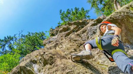 Jonge vrouw klimmer op via ferrata in de Alpen, Zillertal, Oostenrijk