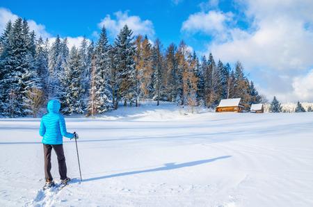Jonge vrouw in blauwe donsjack lopen naar afgelegen berghut tijdens de koude winter Stockfoto