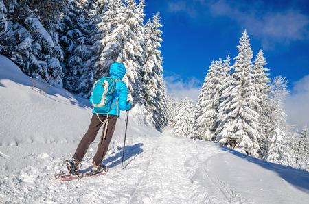Jonge vrouw in donsjack wandelen op sneeuwschoenen in de koude winter landschap, Beskiden, Polen