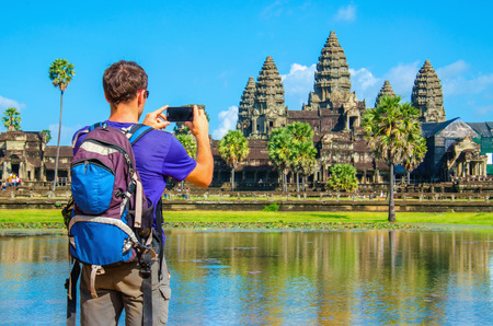 temple: Young man is taking a photo of Angkor Wat temple, Siem Reap, Cambodia Stock Photo