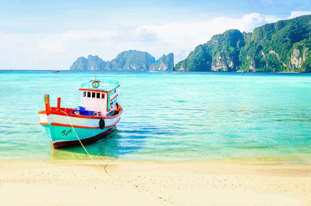 bali province: Red fishing boat on an exotic beach, Phuket, Thailand Editorial