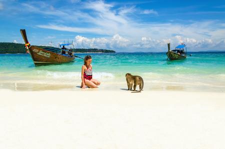 monos: Barco de tailandeses y los monos que esperan el alimento en Monkey Beach, Islas Phi Phi, Tailandia