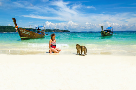 Longtail boot en apen wachten op voedsel in Monkey Beach, Phi Phi eilanden, Thailand Redactioneel