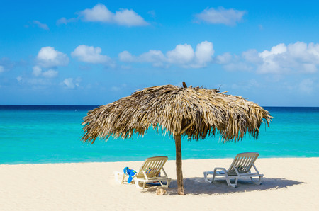 Verbazend tropisch strand met ligbedden en palm paraplu's, gouden zand, azuurblauw water en de blauwe hemel, Caribische eilanden